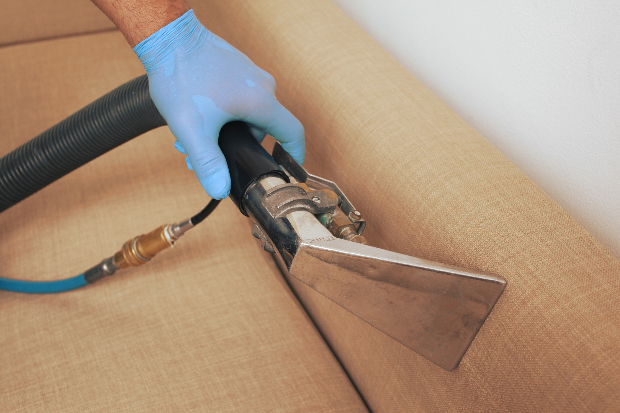 Professional sofa cleaners using a steam cleaner